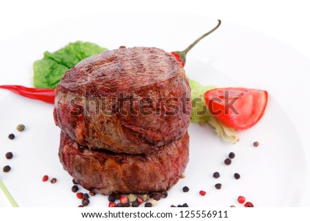 grilled beef fillet medallions on noodles with red hot chili pepper and salad leaf on white plate isolated over white background
