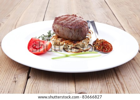 grilled beef fillet medallions on noodles with tomatoes and thyme twigs on white plate over wood