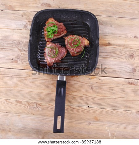 grilled beef fillet strips on a grill plate over wood