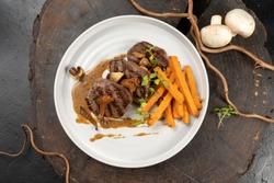 Grilled beef medallions with a side dish of sweet potatoes and mushroom sauce of mushrooms. main hot meat dish. Veal or pork steak.