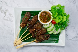 Grilled Beef Skewers chilli Sauce hot  spicy Northeast Thai food style served cucumber and vegetable topview