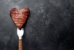 grilled beef steak in the form of a heart on a fork for Valentine's day on a stone background with copy space for your text