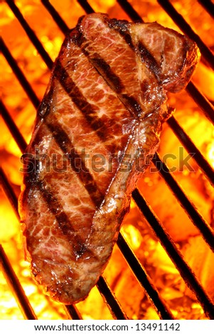 Grilled beef steak on a fire hot barbecue grill.