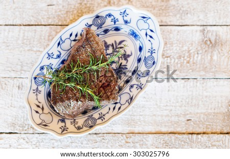 Grilled beef steak on a serving plate with fresh rosemary spring