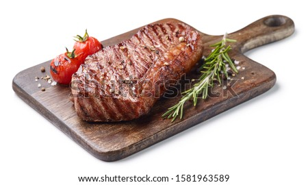 Grilled beef steak on wooden board with tomatoes and rosemary isolated on white background