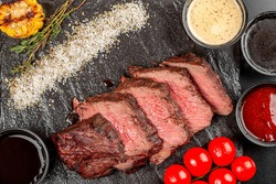 Grilled beef steak pieces on a black background with spices