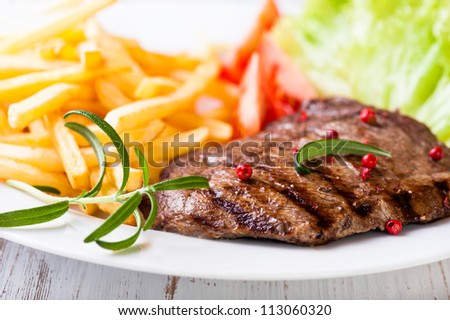 Grilled beef steak with french fries and salad
