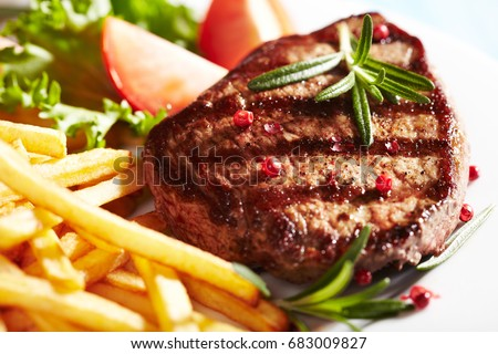 Grilled beef steak with french fries, tomatoes, lettuce and fresh rosemary. Home made food. Concept for a tasty and heart meal. Close up.
