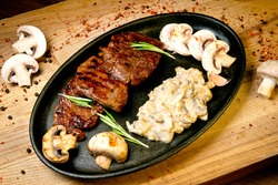 Grilled beef steak with grilled mushrooms and fresh mushroom sauce in a frying pan. on a wooden tray