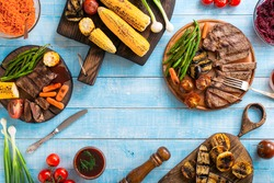 Grilled beef steak with grilled vegetables on wooden blue table with copy space, top view