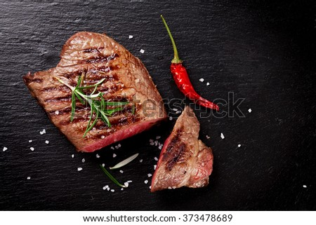 Grilled beef steak with rosemary, salt and pepper on black stone plate. Top view with copy space