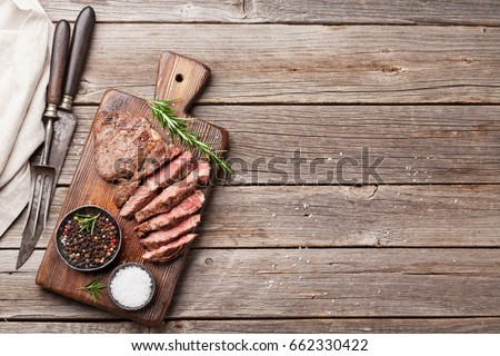 Grilled beef steak with spices on cutting board. Top view with copy space