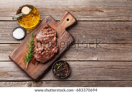 Grilled beef steak with spices on cutting board. Top view with copy space #683370694