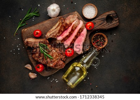 grilled beef steaks with spices on a cutting board on a stone background