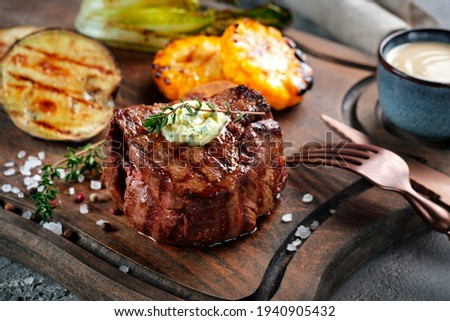 Grilled beef tenderloin steak on a wooden board with butter and thyme. Filet Mignon recipe with vegetables Сток-фото ©
