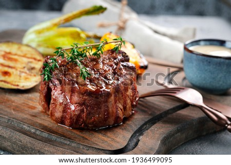 Grilled beef tenderloin steak on a wooden board with grilled vegetables. Filet Mignon recipe concept, selective focus Сток-фото ©