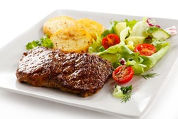 Grilled beefsteak, baked potatoes and vegetables