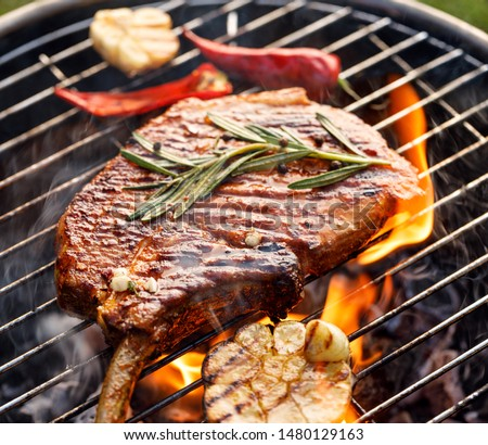 Grilled bone-in pork chop, pork steak, tomahawk in spicy marinade on a flaming grill,  close-up. Barbecue, bbq meat
