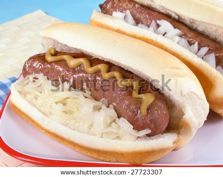 Grilled bratwursts in buns with sauerkraut, mustard, and diced onions.