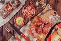 Grilled brazilian sausages on the wooden board with bread, salad, farofa and ingredients - Top view Linguiça churrasco
