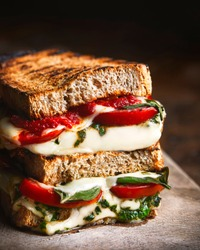 Grilled caprese sandwich on wooden board. Grilled slices of rustic bread with typical Italian ingredients: melted mozzarella cheese, tomatoes, basil leaves, olive oil. Selective focus. Dark background