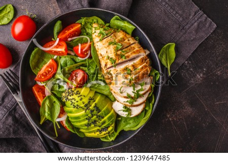 Grilled chicken breast and avocado salad with spinach, tomatoes and Caesar dressing in black plate, dark background.