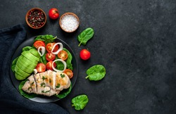 Grilled chicken breast and grilled avocado salad with cherry tomatoes, spinach, in a black plate on a stone background with copy space for your text