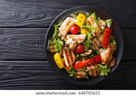 Grilled chicken breast and summer vegetables close-up on a plate on a table. horizontal view from above  #648705631
