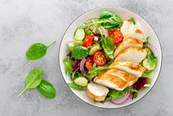 Grilled chicken breast, fillet and fresh vegetable salad of lettuce, arugula, spinach, cucumber and tomato. Healthy lunch menu. Diet food. Top view