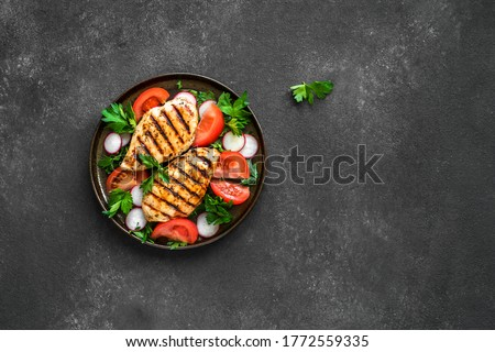 Grilled chicken breast, fillet, steak and fresh vegetable salad, top view, copy space. Healthy keto, ketogenic lunch menu with chicken meat and organic veggies and greens. Сток-фото ©