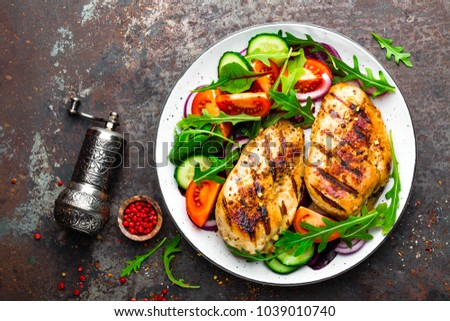 Grilled chicken breast. Fried chicken fillet and fresh vegetable salad of tomatoes, cucumbers and arugula leaves. Chicken meat with salad. Healthy food. Flat lay. Top view. Dark background #1039010740