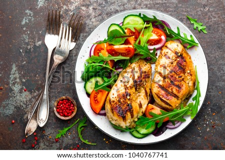 Grilled chicken breast. Fried chicken fillet and fresh vegetable salad of tomatoes, cucumbers and arugula leaves. Chicken meat with salad. Healthy food. Flat lay. Top view. Dark background #1040767741
