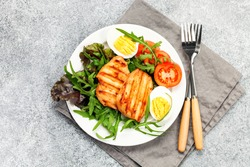 Grilled chicken breast. Fried chicken fillet and fresh vegetable salad of tomatoes, mangold and arugula leaves. Chicken meat salad. Healthy food. Flat lay. Top view. Gray background