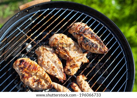 Grilled chicken breast on barbeque, cooking process