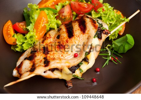 Grilled chicken breast stuffed with mozzarella, sun dried tomatoes, mushrooms and basil