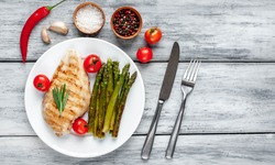 Grilled chicken breast with asparagus and spices on a plate on a wood background with copy space for your text