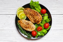 grilled chicken breast with green salad, tomatoes, lemon and rosemary on a black plate. top view