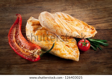 Grilled chicken breast with pepper and tomato on wood