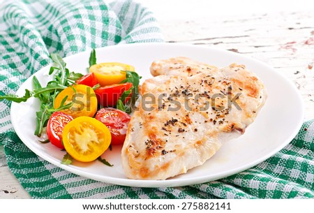 Grilled chicken breasts and vegetables on white plate
