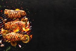 Grilled chicken breasts on a grill plate on black background with copy space, top view. Bbq background