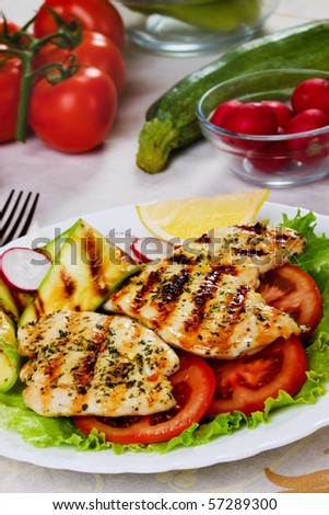 Grilled chicken breasts with tomato, lettuce and zucchini