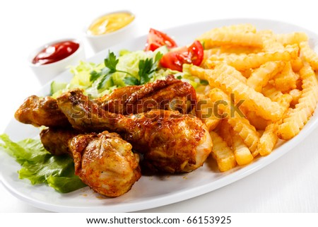 Grilled chicken drumstick, French fries and vegetables
