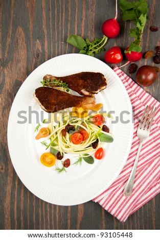 Grilled Chicken Drumsticks Served with Zucchini Salad and Tomatoes - stock photo