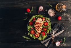 Grilled chicken fillet and fresh vegetable salad of tomatoes and arugula leaves. Healthy food. Black background. Flat lay. Top view.