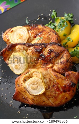 Grilled chicken fillet. Serving grilled poultry meat served on white ceramic plate