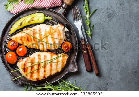Grilled chicken fillets, chili pepper and tomatoes cherry on grill iron pan, fresh herbs - rosemary and parsley, rustic cutlery on gray slate background. top view. copy space