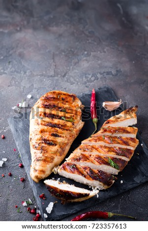 Grilled chicken fillets on slate plate. Gray concrete background. top view. copy space