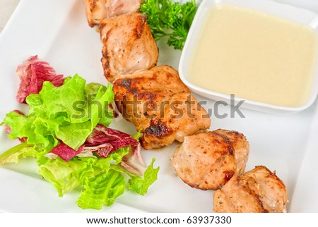 Grilled chicken kebab with sauce and greens on white plate