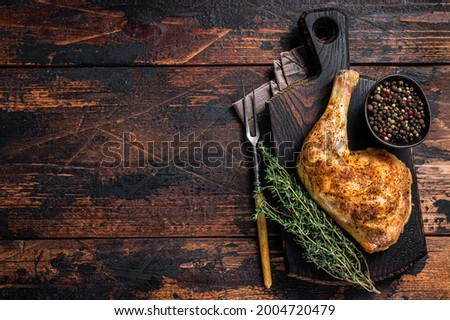 Grilled chicken leg on a wooden board. Dark wooden background. Top view. Copy space Stock fotó ©