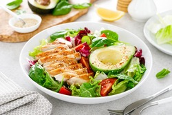 Grilled chicken meat and fresh vegetable salad of tomato, avocado, lettuce and spinach. Healthy and detox food concept. Ketogenic diet. Buddha bowl dish on white background